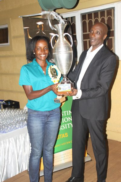 Overall winner of the Inaugural Palm Valley Ladies Open Golf Tournament Namakula Flavia receiving her trophy from Police Boss Gen. Kale Kayihura.