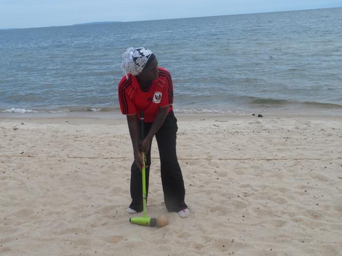 A wood ball player takes a shot during the Beach wood ball circuit at sports Beach Entebbe.