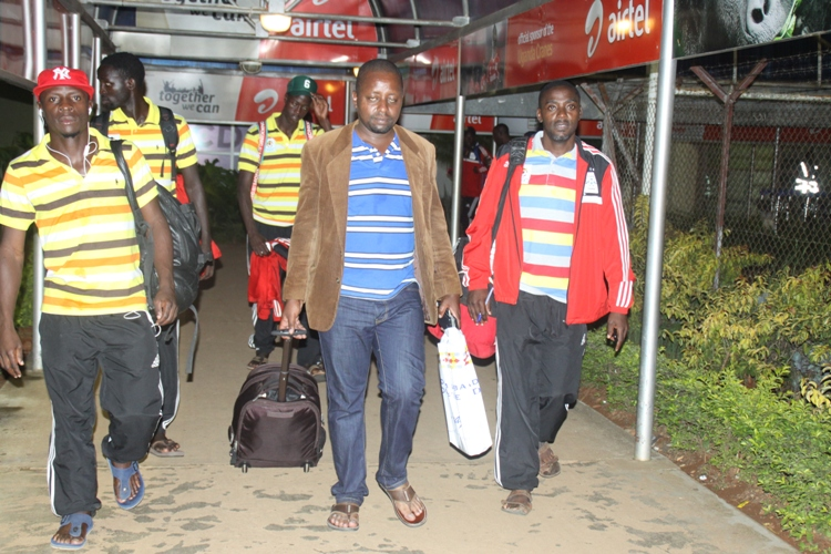 Fufa Head of delegation Darius Mugoye (centre) with cranes players shortly after arriving at Entebbe International Airport.