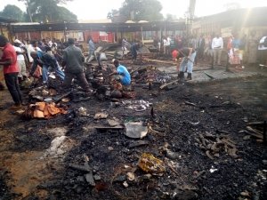 Vendors pick a few remains from the ashes after the market was burnt to ashes.
