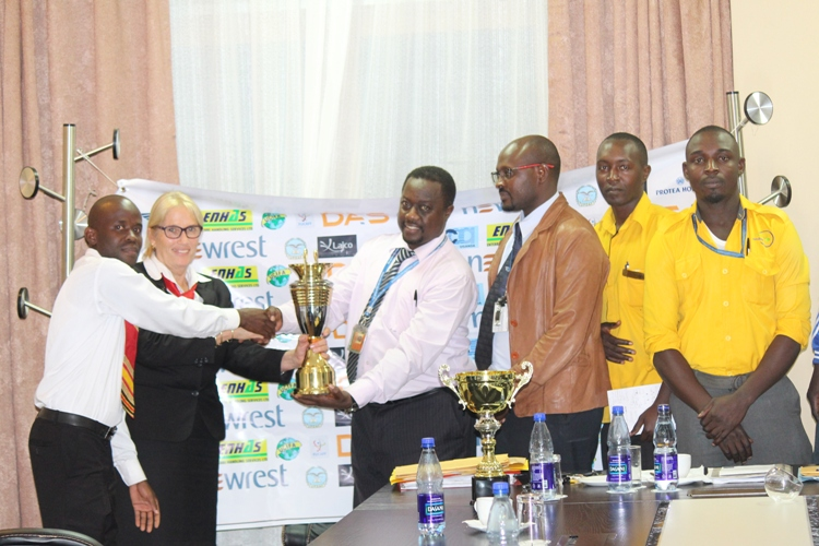 Protea's Sharon Haris hands over the new trophies to league chairman Tom Byarugaba.