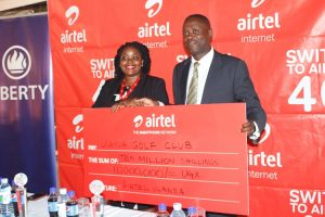 U.G.C Captain Joseph Bagabo displays the Shs10m dummy cheque from Airtel with Airtel Brand and Communications Manager Remmie Kisakye.