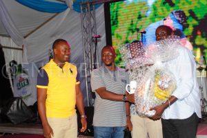 Kiddu Kenneth Receives His prizes including a Mug from Entebbe Club Chairman Twinemanzi Tumubweine.