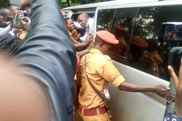 A prison warder closes the door of a van in which Dr Stella Nyanzi was bundled shortly after she collapsed following a court order to set her free on February 20, 2020. PHOTO BY BETTY NDAGIRE