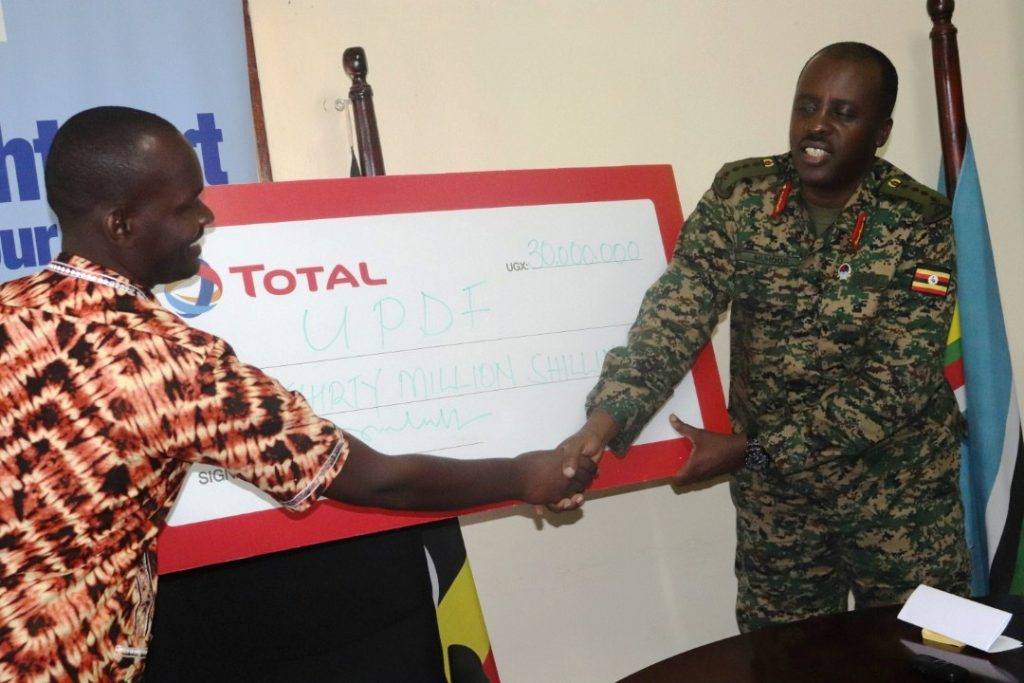 CDF General David Muhoozi receives UGX30m cheque from Total Uganda's Managing Director, Obi Imemba as part of Tarehe Sita celebrations