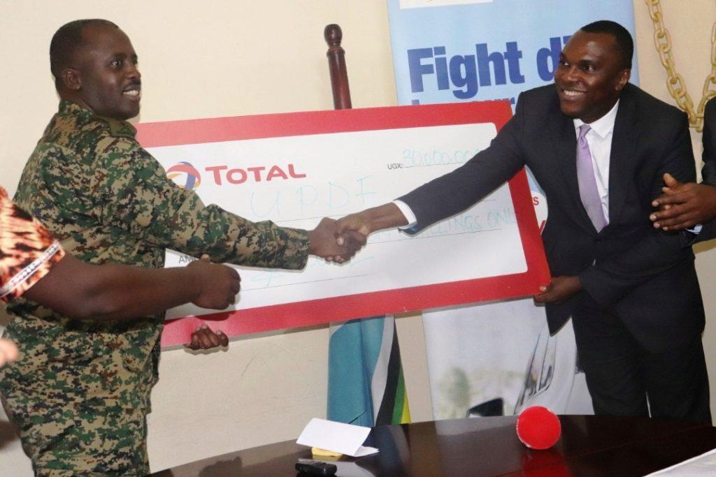 CDF General David Muhoozi receives UGX30m cheque from Total Uganda's Managing Director, Obi Imemba as part of Tarehe Sita celebrations