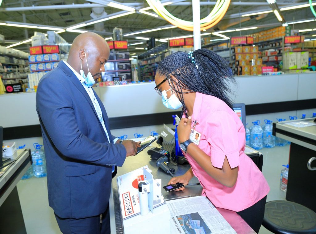 A customer pays at the till using Airtel Money Pay assisted by a Game Store Executive
