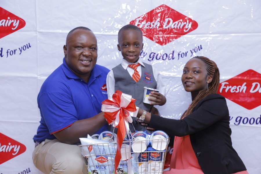 A school going child (C) flanked by Vincent Omoth-Marketing Manager Fresh Dairy (L) and his mother (R) holds up Fresh Dairy flavoured yoghurt. Yoghurt is a healthy and nutritious choice for homeschooled children